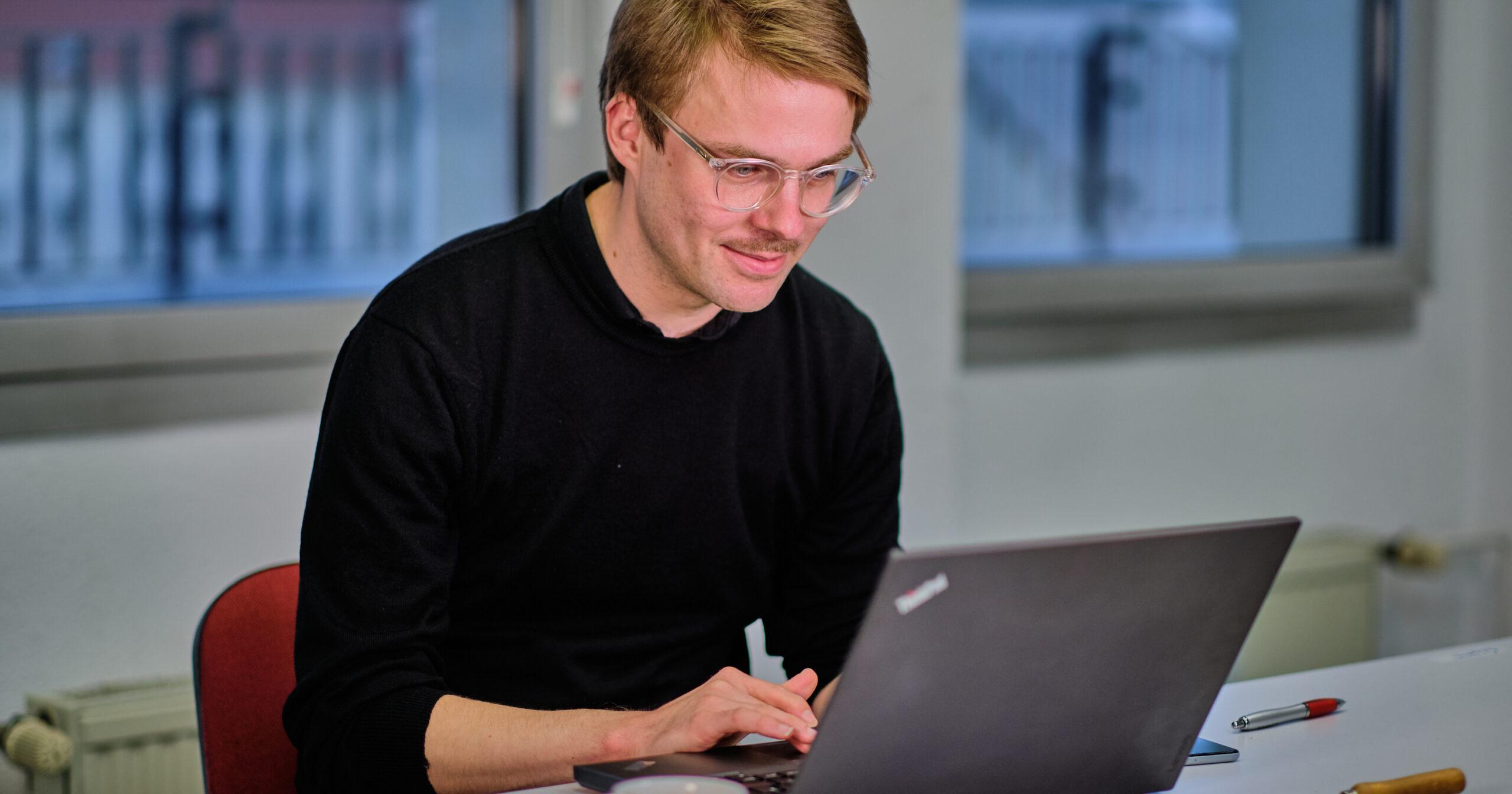 Stefan Kunath auf einem Laptop tippend