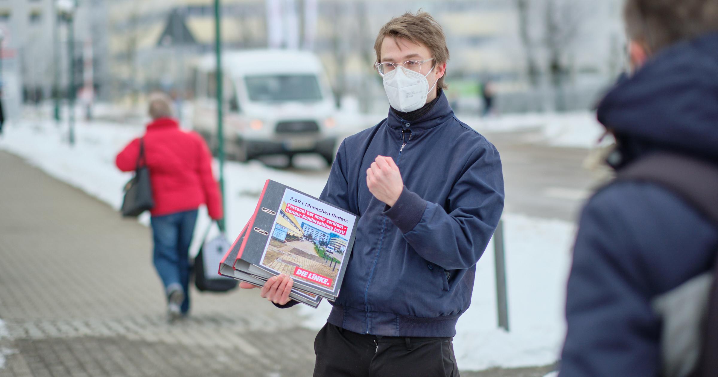 Stefan Kunath hält die Ordner mit allen Unterschriften vor dem Klinikum Frankfurt (Oder) in der Hand