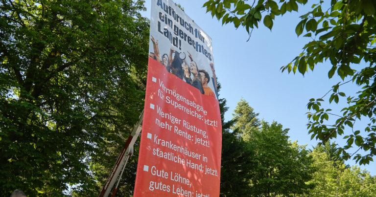 Banner mit den Forderungen der Gerechtigkeits-Tour